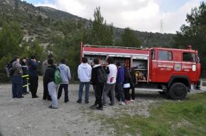 Εθελοντές δασοπροστασίας και μαθητές δίπλα σε πυροσβεστικό όχημα.